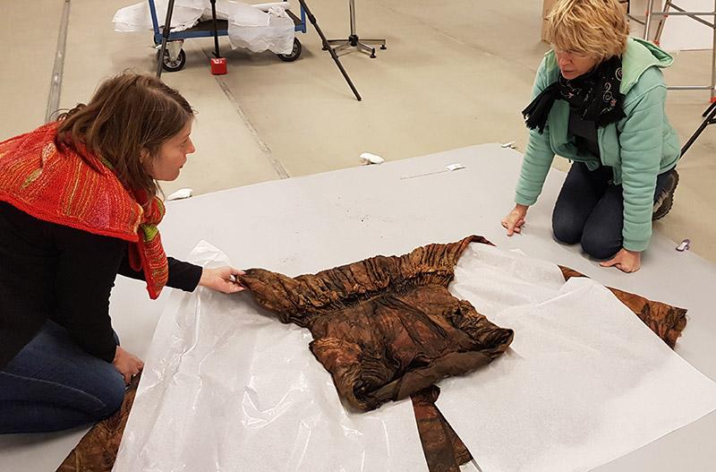 De zijden jurk gevonden in het scheepswrak moet voorzichtig gehanteerd worden.